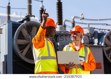 technical workers discussing work at electrical substation