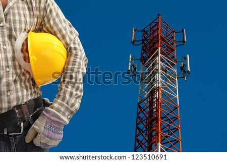 technician against telecommunication tower, painted white and red in a day of clear blue sky. - stock photo