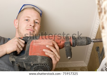 Technician air conditioning drills the wall. Work on installing a new air conditioner in the apartment. - stock photo