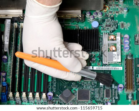 technician brushing dust of mother board - stock photo