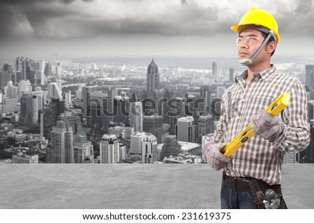 technician builder in protective safety equipment goggles hard hat and water level working at high building construction site against urban scene balcony over looking city dusky before rain falling - stock photo