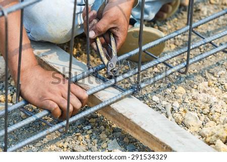 technician bundle wire steel rod for construction job - stock photo