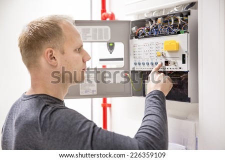 Technician checks fire panel in data center - stock photo