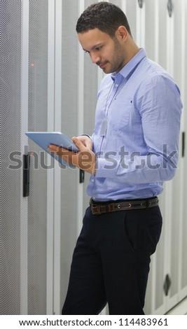 Technician doing data storage in lighted hallway - stock photo