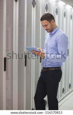 Technician doing maintenance with tablet pc in lighted hallway - stock photo