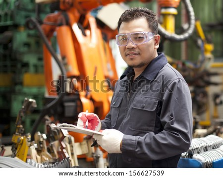 Technician  engineer holding a notepad with robot machine on background - stock photo
