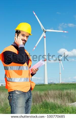 Technician Engineer in Wind Turbine Power Generator Station talk at phone, Italy - stock photo
