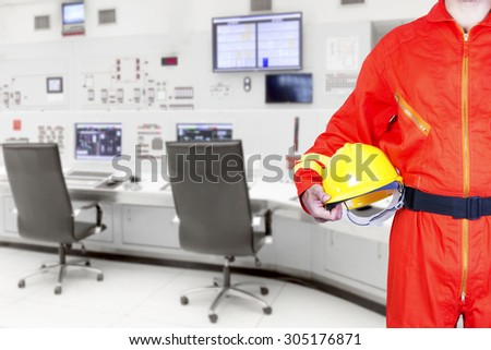 Technician holding hard hat for working at control room of a modern thermal power plant - stock photo