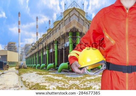 Technician holding hard hat for working at cooling tower of Industrial power plant  - stock photo