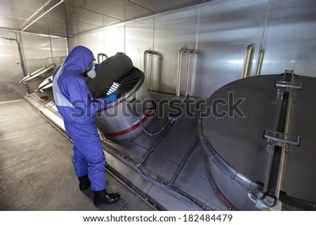Technician in mask,  blue uniform  checking technological system with tablet in high tech environment  - stock photo