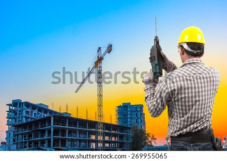 technician in protective safety equipment with drill and tool belt working at building construction site against beautiful sky sunset