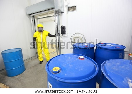 technician in protective uniform checking barrels with toxic substance in plant - stock photo