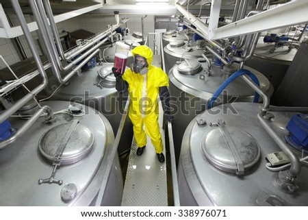 technician in protective uniform,mask,goggles,gloves and wellies checking technological process - stock photo