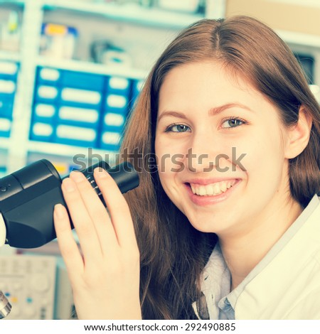 technician in the laboratory using a microscope, girl smiling - stock photo