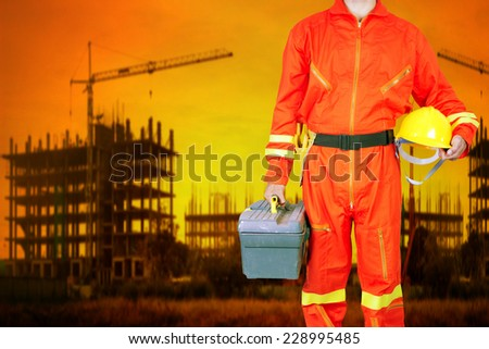 technician in uniform holding toolbox working at high building construction site against beautiful sunset - stock photo