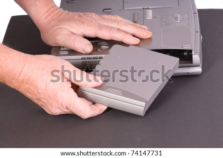 Technician installing a battery into a laptop - stock photo