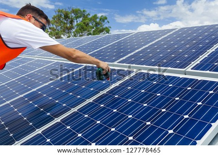 Technician installing solar panels on factory roof - stock photo