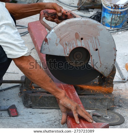 Technician is cutting steel using electric cutting steel and sparks during operation.  - stock photo