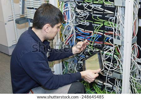 Technician is cutting wires using pliers of server in data center  - stock photo