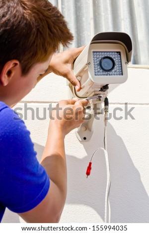 technician man setup cctv camera on wall - stock photo