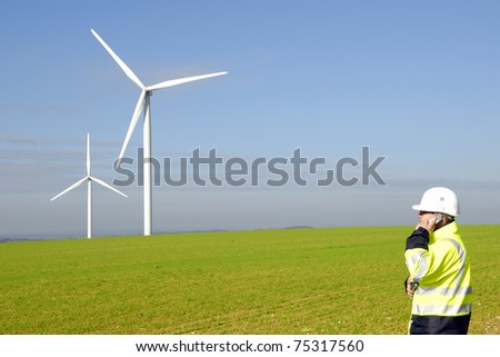 technician on the phone with windmills on the background - stock photo