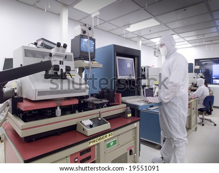 Technician operating various wafer testing equipment in clean lab