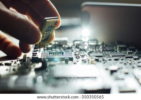 Technician plug in CPU microprocessor to motherboard socket. Workshop background