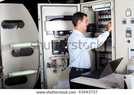 technician repairing industrial machine with laptop computer - stock photo