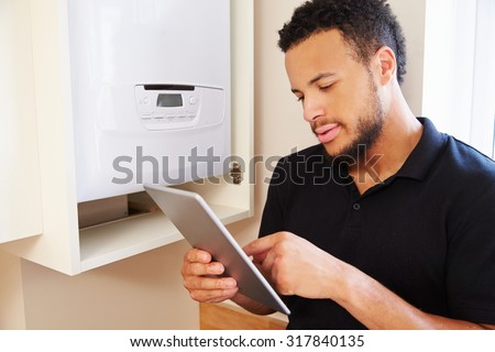 Technician servicing a boiler using tablet computer