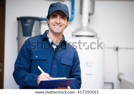 Technician servicing an hot-water heater - stock photo
