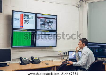 Technician sitting in office running diagnostics in large data center - stock photo