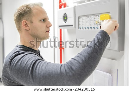 Technician test fire panel in data center - stock photo