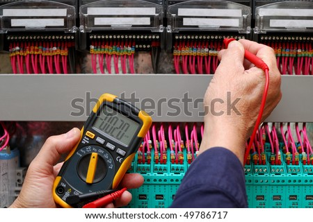 Technician testing a control panel wiht measurement instrument, close-up - stock photo