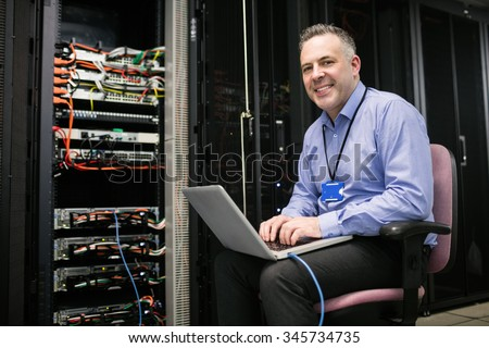 Technician using laptop in server room at the data centre - stock photo