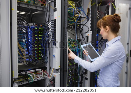 Technician using tablet pc while analysing server in large data center - stock photo