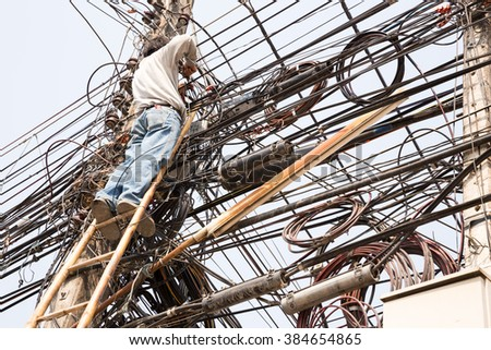 Technician wiring fiber optic cable access to the chaos of cables, Thailand. - stock photo