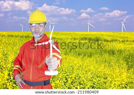 technician with holding wind turbine in a flower field eco power concept - stock photo