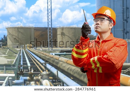 Technician with radio communication for working at pipe line connection to oil tanks in petrochemical oil refinery