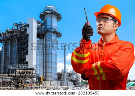 technician with radio communication in action and equipments and machinery with modern thermal power plant in refinery - stock photo