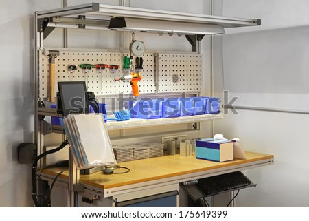 Technician workbench desk with tools and shelves - stock photo