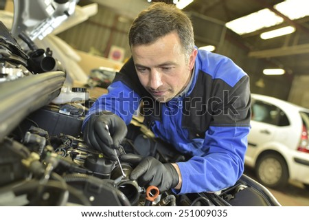Technician working in auto repair shop - stock photo