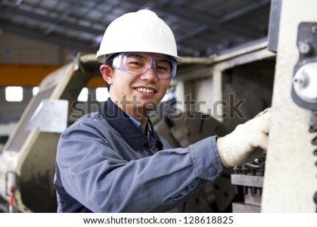 Technician working in factory front of milling cutting machine - stock photo