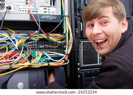 Technician working on server rack looks fun end enjoyed - stock photo