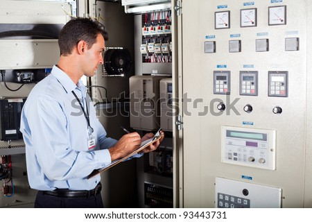 technician writing down modern computerized machine setting data