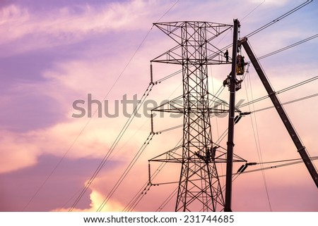 Technicians working on  electricity pole under light of  evening. - stock photo