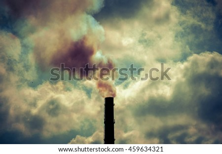 technogenic contrasting background tip of the black silhouette pipe with smoke sky with bright clouds and sun backlight