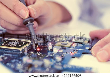 Technological background with closeup on tester checking motherboard. Toned image. Shallow DOF, exact focus on the tester tip - stock photo