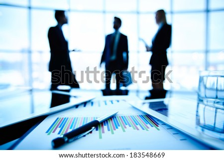 Technological devices and financial document at workplace on background of three business partners discussing ideas
