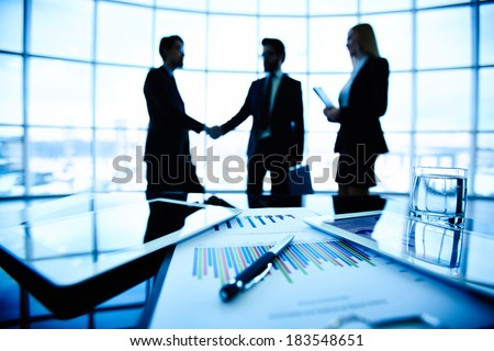 Technological devices, financial document with pen, glass of water at workplace on background of three business partners striking deal - stock photo