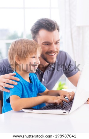Technologies become easier. Cheerful father and son looking at the laptop while little boy typing something on keyboard and smiling